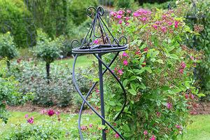 Fantazyjny obelisk z metalowych, giętych drutów przeznaczony dla pnących róż