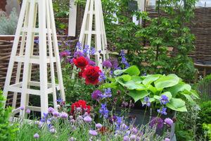 Tradycyjne obeliski drewniane pomalowane na jasny kolor służą jako ozdoba ogrodu