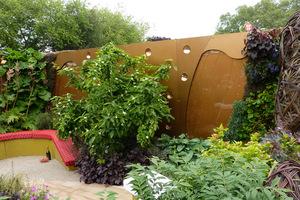 Ciekawa faktura i kolor muru w połączeniu z ogrodem w pionie tworzy przemiły zakątek do odpoczynku