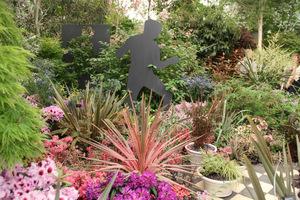 Kordyliny w towarzystwie różaneczników, lnu nowozelandzkiego i kwitnących krzewów (Chelsea Flower Show)
