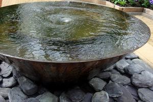 Element wodny przyozdobiony kamieniami i maskujący kratkę