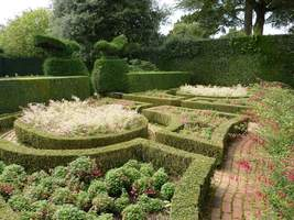 Formalny ogród zamknięty w bukszpanach z fuksjami w środku. Strzegą go dwa ptaki z cisa kłaniające się sobie