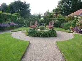 W centrum Walled Garden znajduje się okrągły, podniesiony i obrośnięty staw z kwiatami lata ustawionymi na cokole