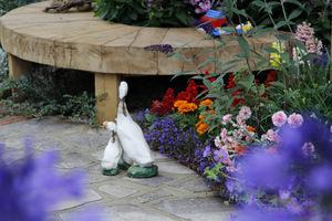 Drewniana ławka i gadżety ogrodowe w postaci figurek ptactwa domowego