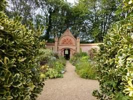"""Brama z herbem miasta Manchester i motto dla dwóch pracowitych ogrodników: """"Consilio et Labore"""""""