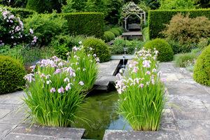 Regularny zbiornik w ogrodzie geometrycznym z wąskim kanałem płynącym