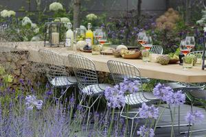 Wokół stołu ustawiono krzesła wykonane z drucianej siatki