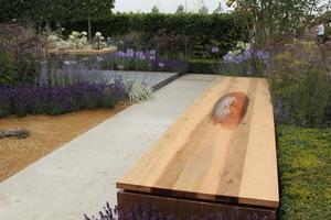 Komunikacja po ogrodzie odbywa się po betonowej płycie w odcieniu lekko beżowym, a pomiędzy roślinami na rabatach wysypano ciepły, beżowy żwirek