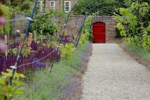 Do wnętrza ogrodowego prowadzą jaskrawoczerwone drzwi