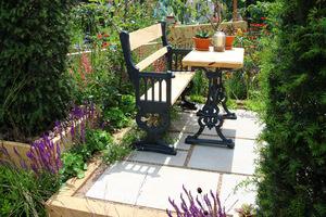 Małe prostokątne patio z oryginalnymi mebelkami wśród bujnej roślinności