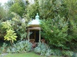 Mała drewniana świątynia z kopułą pokrytą miedzianą blachą.