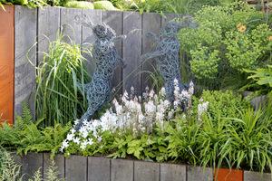 Drewniane ogrodzenie z rzeźbami i bujną roślinnością