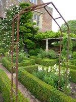 Zakątek z meblami w narożniku romantycznego ogrodu białego w Sissinghurst